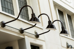 Elegant black outdoor lamps above windows on Birks Building
