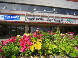 Bright flower container gardens line the entrance to 1422 Kensington Road, for lease by Melcor REIT.