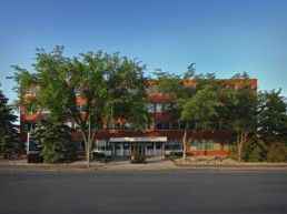 Regina Saskatchewan, this red building sits among green trees as an office property owned by Melcor REIT.