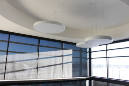 Modern light-fixtures hang in building at The Village at Blackmud Creek