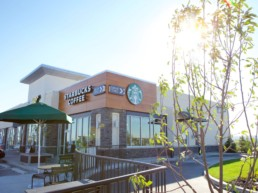 Starbucks building location at The District in North Deerfoot Caglary, exterior property with umbrella and trees on the patio in the sunlight. Part of our property portfolio for Melcor REIT,.